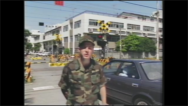 1990s: U.S soldier stands in front of a railroad crossing with yellow barriers and red flashing lights. U.S. soldier watches a train go by.