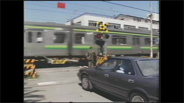 1990s: U.S soldier stands in front of a railroad crossing with yellow barriers and red flashing lights. U.S. soldier watches a train go by very quickly.