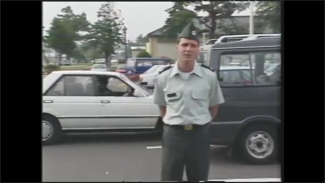 1990s: Cars almost get in a collision in a parking lot as one car backs out. U.S, soldier in uniform explains rate of accidents in parking lots in Japan.