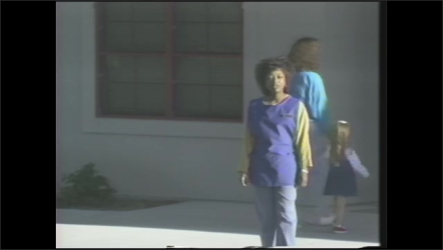 "1990s: ""child development center"" sign on building, woman walks up to building, talks, greets woman with girl walking into building, woman talks in front of photo of soldier and girl"