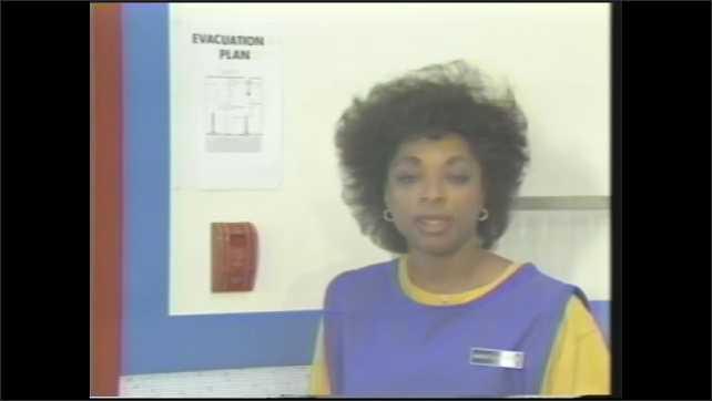 """1990s: woman in smock with clipboard talks, points to """"evacuation plan"""" sign above fire alarm on wall,"""