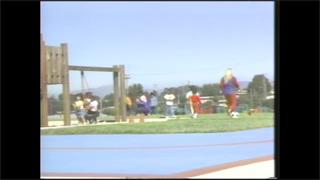1990s: girl slides down playground slide into sand, woman in smock with clipboard talks, puts arm around girl, children run, play, ride tricycle on playground, girl in sandbox, children swing on tire