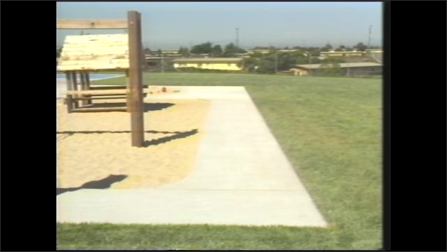 1990s: tube slide and climbing structure on playground, woman in smock with clipboard walks on playground path, playground slide and structures with sand, platforms with trees