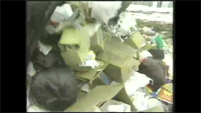 1980s: Man stands in front of garbage can, talks. Garbage truck unloads garbage on to landfill pile.