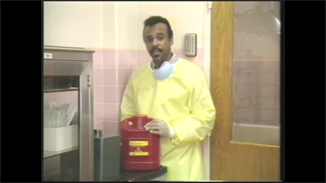 1980s: Man walks up to hard red container, secures lid on container, picks up container, walks away.