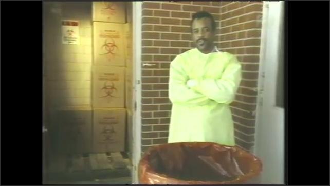 1980s: Man seals biohazard box. Man stands outside biohazard area, talks. Stacks of biohazard boxes.