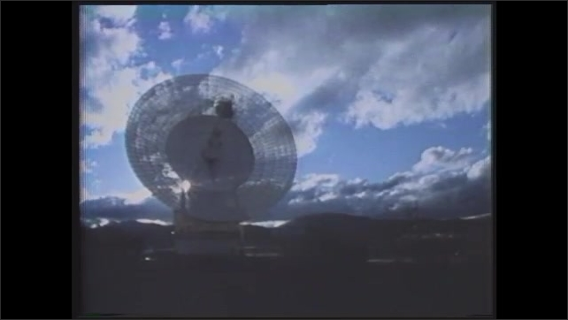1980s: Animated spacecraft moves past sun.  Satellite dish.  Sunset.