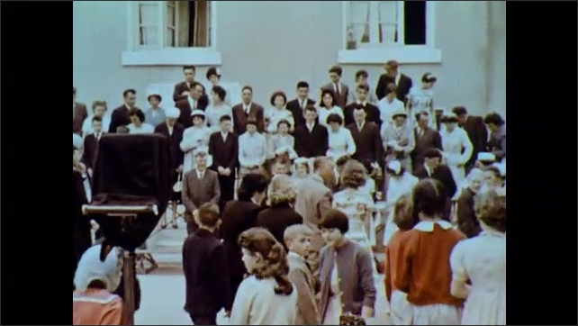 1960s: Group of people gather outside cathedral for group wedding photo. People pose for photograph. Man and woman watch while talking.