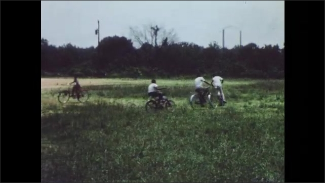 1960s: UNITED STATES: boy sits on climbing frame. Children play on bikes outdoors.