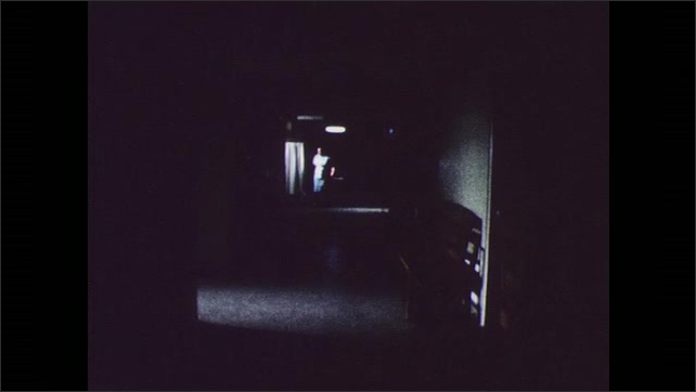 1960s: UNITED STATES: hospital corridor at night. Lady walks along dark corridor.