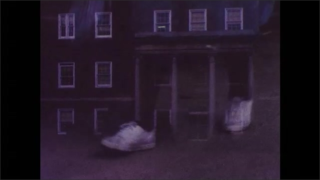 1960s: UNITED STATES: lady leaves building at night. Hospital building in dawn light. Feet walk along pavement.