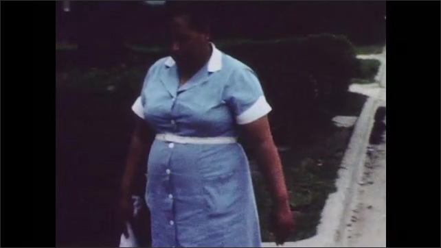 1960s: UNITED STATES: lady walks along street. Lady walks home after work. Lady arrives at home