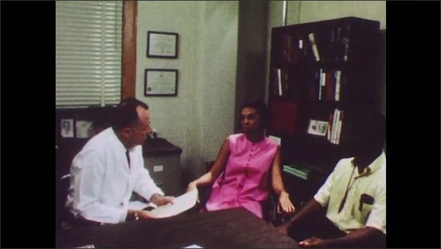 1960s: UNITED STATES: doctor speaks with lady in office. Lady and man meet with physician. Close up of lady's face.