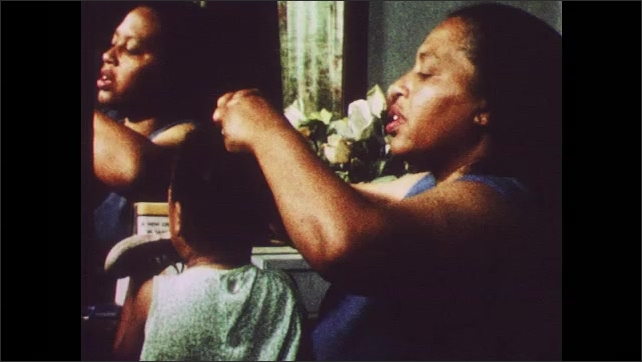 1960s: UNITED STATES: lady does child's hair by mirror. Lady ties bow in baby's hair