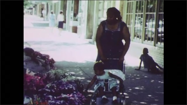 1960s: UNITED STATES: lady stands by shop window. Lady pushes stroller in street. Child pats flowers.