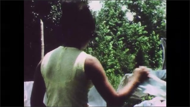 1960s: UNITED STATES: children help lady with washing in garden. Lady sorts washing