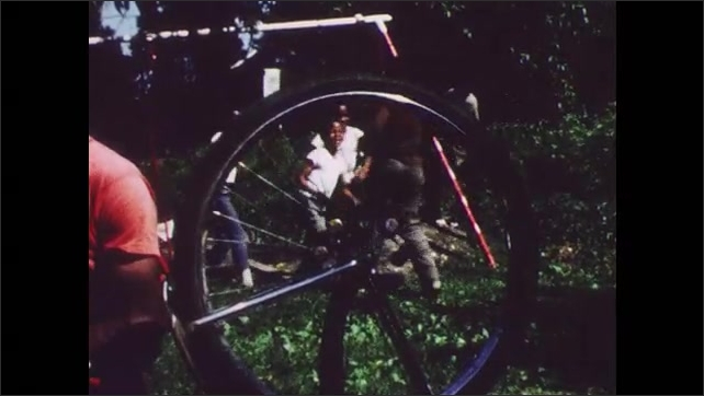 1960s: Man works on bicycle.  Boys play in yard.