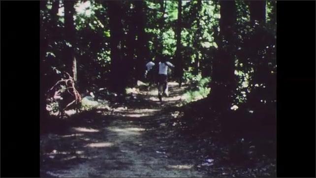 1960s: Group of boys runs through woods.