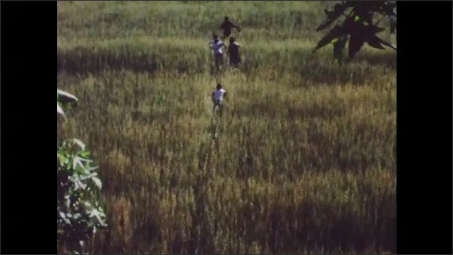 1960s: Group of boys run through field.  Boy waves hat over his head.