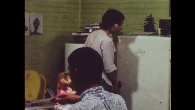 1960s: Woman drives car down road.  Kitchen.  Woman closes refrigerator.  Family photos.  Woman does laundry.  Children play with dog on porch.