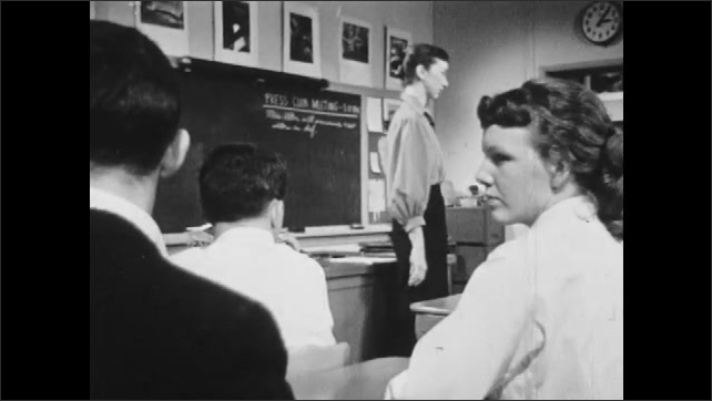 1950s: Students clap at desks in classroom. Boy in sports coat looks concerned. Teacher speaks to class. Girl talks to boy at desk. Boy in loose clothing stands before classroom and speaks.
