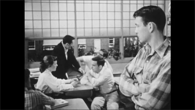 1950s: Boy in loose clothing looks at group of taking students and thinks to self. Boys stand in aisle of desks and talk.