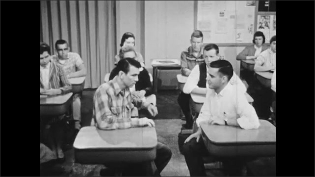 1950s: Students clap at desks in classroom. Boy in loose clothing stands and slowly walks to front of class.