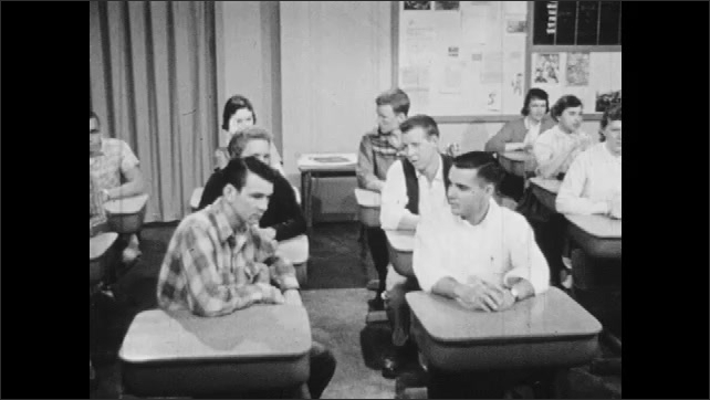 1950s: Teacher looks around and thinks to self. Students applaud at desks. Teacher speaks and walks from desk. Boy in loose clothing walks to front of classroom.