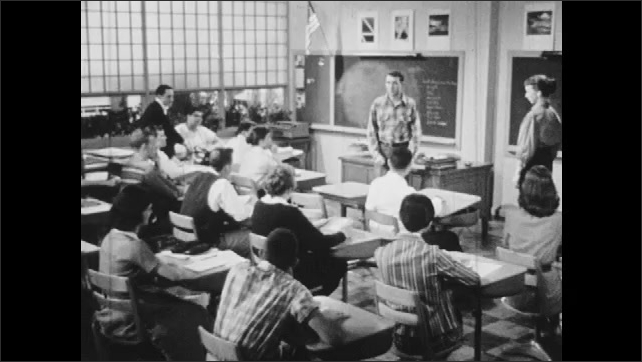 1950s: Teacher thinks to self. Boy in loose clothing stands before class and speaks.