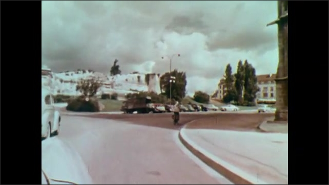 1960s: Pan to woman by river writing letter. Tracking shot, driving through neighborhood.