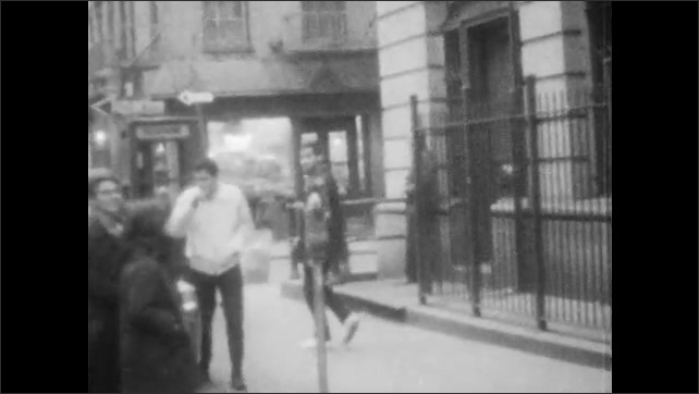1960s: Young man walks downstairs and out of building.  Man greets men talking outside.  Man walks down street to liquor store.
