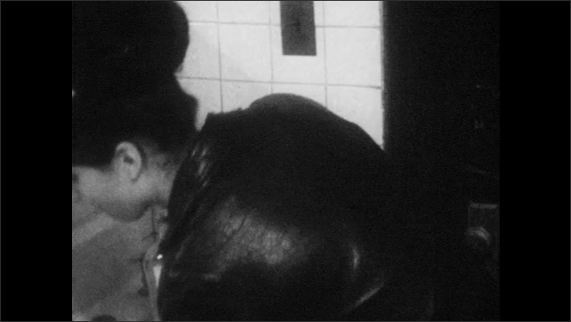 1960s: Young men and women dance.  Woman drinks from liquor bottle in bathroom.  Woman finishes drinking and throws away bottle.
