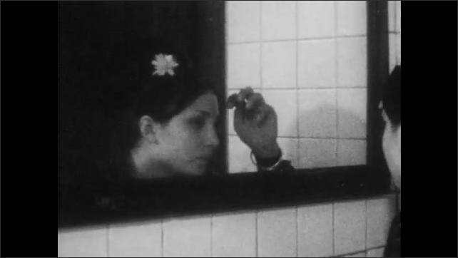 1960s: Young woman dabs water on face and looks in bathroom mirror.