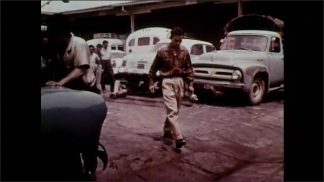 1960s: UNITED STATES: man looks for larvae in stagnant water and breeding grounds. Yellow Fever man sprays containers.
