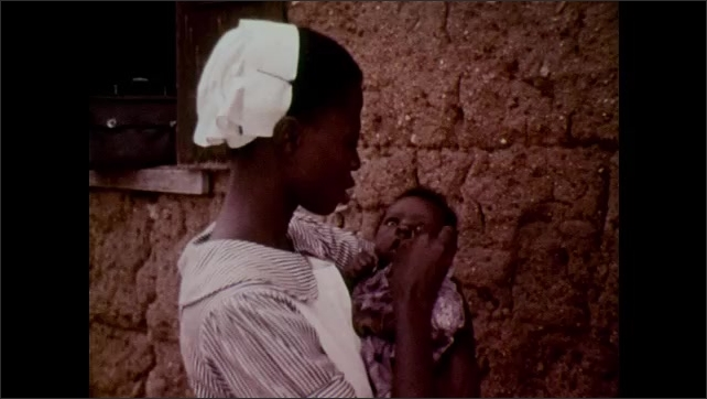 1960s: UNITED STATES: lady treats people in village. Lady holds baby. Local auxiliaries treat people in village. Man examines patient.