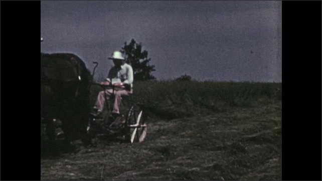 1950s: Horses pull farmer on wheeled mower. Sickle blade of mower slices down tall grass. Horses pull farmer and mower along field of tall grass.