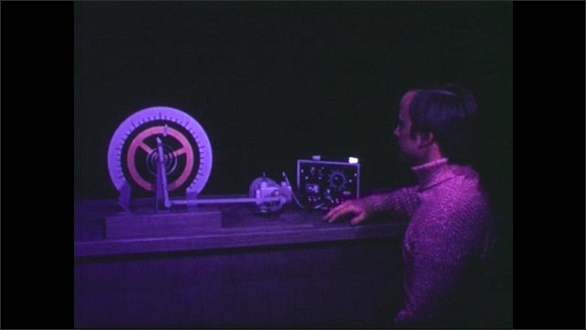1960s: Man closes clapboard, walks off screen, man sits next to equipment on table, man enters behind table, zoom in on man, colored lights shine on man's face.