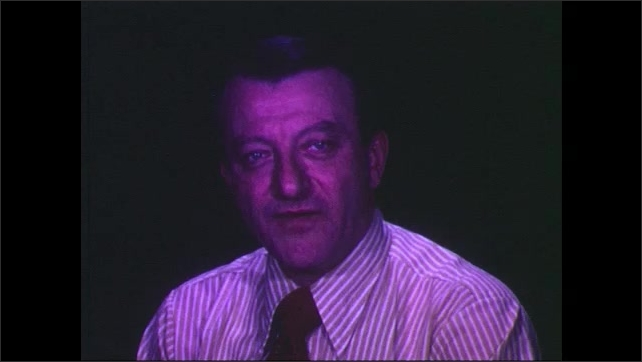 1960s: Close up, hands close clapboard, man talking, colored lights shine on man's face, man puts on glasses.