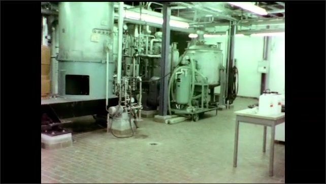 1970s: Metal rails and stairs surrounding cannister. Metal pipes and tanks in laboratory. Large steel pressure cannister in lab.