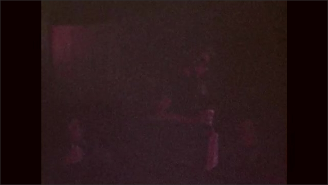 1970s: Boy carries box of popcorn and drink through darkened theatre. Boy bumps into others in dark. Boy eats and drinks in movie theatre seat.