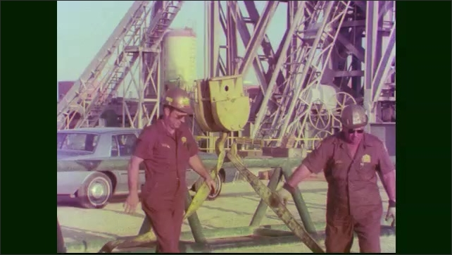1970s: Two workers attach rigging for a drill pipe to a crane hook. The two workers step away.
