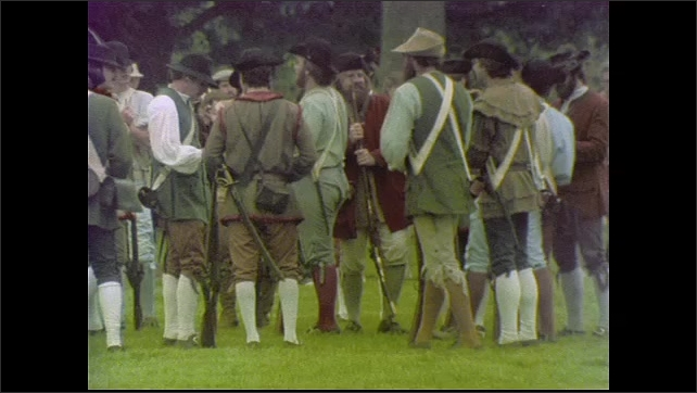 1970s: UNITED STATES: British flag flying. Coat of arms on building. Men dressed in reenactment costume. Men load guns by stone building.