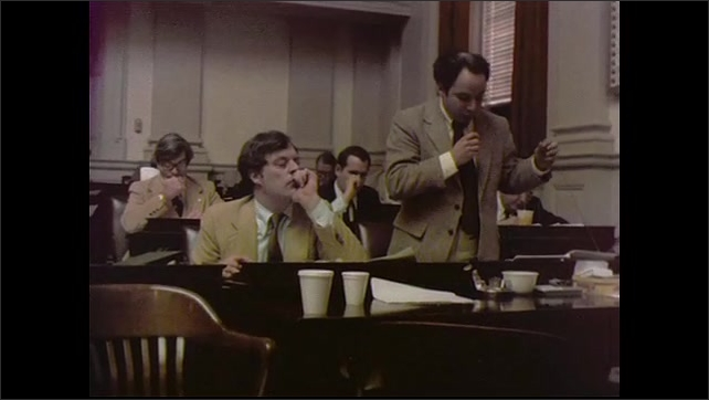 1970s: UNITED STATES: man stands to present at meeting. Lady and man share paper. Man sits at table in meeting. Coffee cups on table.