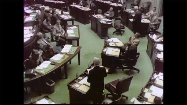 1970s: UNITED STATES: side profile of man smoking pipe at meeting. Man speaks at meeting. Members sit in meeting.