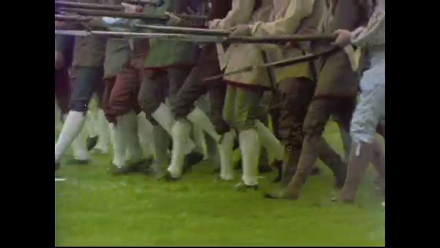 1970s: UNITED STATES: men in outfits march with guns. Gravestones in church yard. Close up of feet. Horse and cart passes building. St Johns sign in window