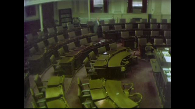 1970s: UNITED STATES: man stands in General Assembly hall building. Man speaks to camera. Seats in meeting room.