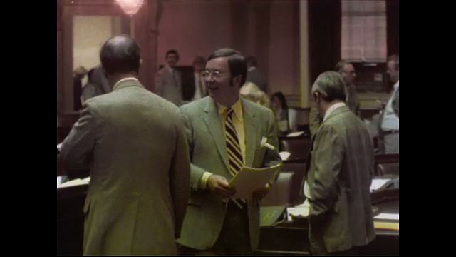 1970s: UNITED STATES: man speaks to people in room. Man presents papers to man at booth. General Assembly meeting room