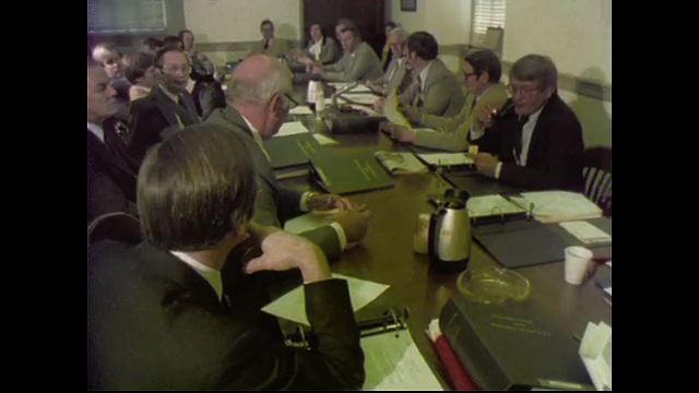 1970s: UNITED STATES: men sit around board room table. Senate Room B sign on wood. Members sit in conference