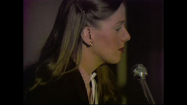 1970s: UNITED STATES: lady speaks into microphone on podium. Side profile of lady speaking. Members sit at tables. Man speaks to camera.
