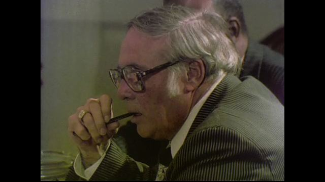 1970s: UNITED STATES: side profile of man smoking pipe at meeting. Man speaks at meeting. Members sit in meeting.